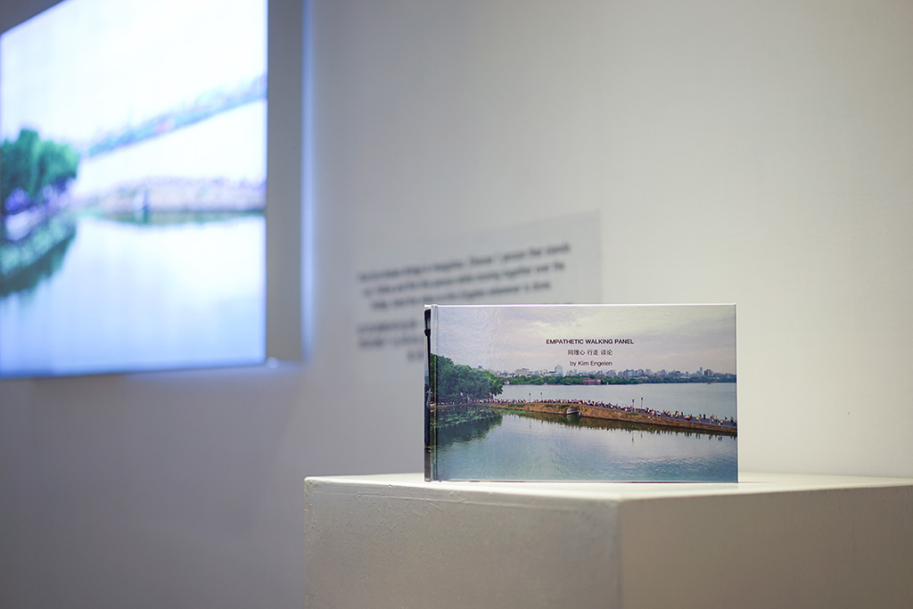 Kim Engelen, Bridge-Performance, Empathetic Walking Panel, light-box: 120x80x8 cm (47.24x31,50x3.15 inches), book: 17x30 cm (6.69x11.81 inches), selfie-stick and drone video recording, 2018